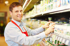 Salesman organizing dairy products in supermarket. Smiling salesman organizing dairy products in supermarket shelf Royalty Free Stock Images