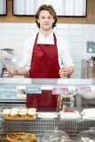 Salesman at the pastry shop. Portrait of a handsome salesman in red apron standing at the showcase of the modern pastry shop stock photography