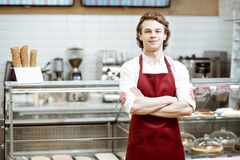 Salesman at the pastry shop. Portrait of a handsome salesman or waiter in red apron standing in the pastry cafe with shop-front on the background stock photography