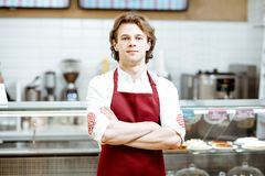 Salesman at the pastry shop. Portrait of a handsome salesman or waiter in red apron standing in the pastry cafe with shop-front on the background royalty free stock images
