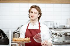 Salesman with pie at the pastry shop. Portrait of a handsome young salesman in red apron standing with fresh pie at the modern pastry shop royalty free stock photo