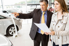 Salesman pointing a car to a client. At new car showroom Stock Images