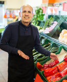 Salesman posing near different vegetables. Charming senior salesman posing near display with different vegetables in supermarket Stock Images