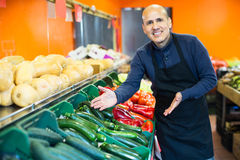 Salesman posing near different vegetables. Portrait of salesman posing near display with different vegetables in supermarket Royalty Free Stock Images