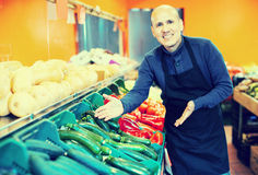 Salesman posing near different vegetables. Portrait of salesman posing near display with different vegetables in supermarket Stock Images