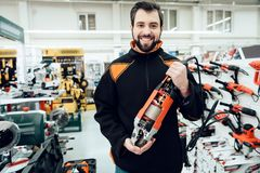 Salesman is posing with new disc grinder in power tools store. stock images