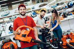 Salesman is posing with new leaf blower with couple of clients in background in power tools store. Salesman in red shirt and baseball cap is posing with new stock image