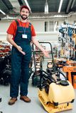 Salesman is posing with plate compactor on foreground in power tools store. stock images