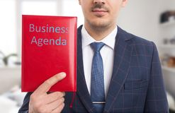 Salesman presenting business agenda. With red covers and blue text royalty free stock image