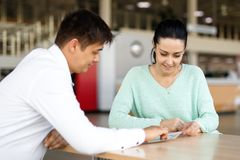 Salesman presenting car to clients. Salesman presenting new car to clients in the background of dealership royalty free stock images