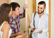 Salesman presents his project standing near the entrance door Stock Image