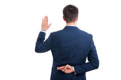 Salesman promising an oath with crossed fingers. Behind his back as false statement concept isolated on white background Royalty Free Stock Photo
