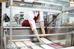 Salesman putting ice cream into the refrigerator. Salesman putting trays with ice cream into the showcase refrigerator at the pastry shop royalty free stock photography