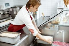 Salesman putting ice cream into the refrigerator. Salesman putting tray with ice cream into the showcase refrigerator in the shop royalty free stock image