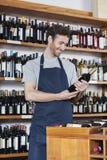 Salesman Reading Label Of Wine Bottle In Store Stock Photos