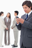 Salesman reading text message on cellphone with team behind him Stock Photo