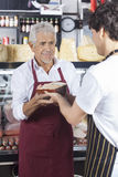 Salesman Receiving Cheese From Colleague In Grocery Shop Royalty Free Stock Images