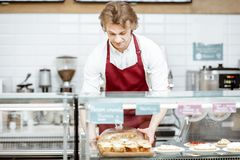 Salesman with pie at the pastry shop. Salesman in red apron putting fresh pie into the refrigerator of the showcase at the modern pastry shop stock image