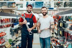 Salesman and bearded client posing with giant wrenches in power tools store. royalty free stock images