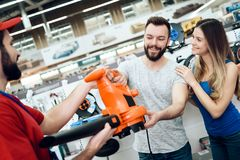 Salesman is giving new leaf blower to couple of clients in power tools store. royalty free stock photo