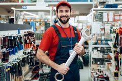 Salesman is posing with new giant wrench in power tools store. Salesman in red shirt and baseball cap is posing with new giant wrench in power tools store Royalty Free Stock Photos