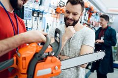 Salesman is showing bearded client new chainsaw in power tools store. Salesman in red shirt and baseball cap is showing bearded client new chainsaw in power stock photos