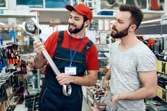 Salesman is showing bearded client new giant wrench in power tools store. Salesman in red shirt and baseball cap is showing bearded client new giant wrench in Royalty Free Stock Images