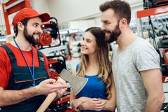 Salesman is showing couple of clients new axe in power tools store. Salesman in red shirt and baseball cap is showing couple of clients new axe in power tools Royalty Free Stock Photography