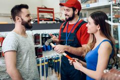 Salesman is showing couple of clients new hammer in power tools store. Salesman in red shirt and baseball cap is showing couple of clients new hammer in power Stock Photo