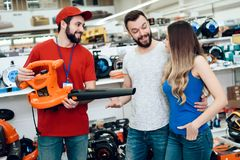 Salesman is showing couple of clients new leaf blower in power tools store. Salesman in red shirt and baseball cap is showing couple of clients new leaf blower royalty free stock image