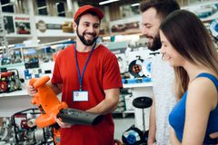 Salesman is showing couple of clients new leaf blower in power tools store. Salesman in red shirt and baseball cap is showing couple of clients new leaf blower royalty free stock images