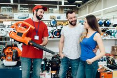 Salesman is showing couple of clients new leaf blower in power tools store. Salesman in red shirt and baseball cap is showing couple of clients new leaf blower stock photography