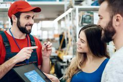 Salesman is showing couple of clients new toolbox in power tools store. Salesman in red shirt and baseball cap is showing couple of clients new toolbox in power Stock Photo