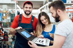 Salesman is showing couple of clients new toolbox in power tools store. Salesman in red shirt and baseball cap is showing couple of clients new toolbox in power Royalty Free Stock Photos