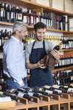 Salesman Removing Wine Bottle From Bag For Customer Stock Image