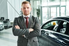 Salesman at salon. Portrait of confident salesman standing with arms crossed at auto salon stock images