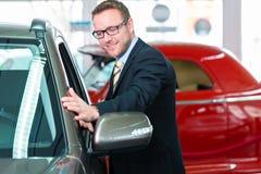 Salesman selling car at dealership Royalty Free Stock Photos