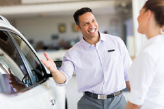 Salesman selling car. Friendly salesman selling car to a customer in showroom Royalty Free Stock Photo