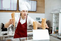 Salesman selling ice cream in the shop. Handsome salesman in apron and hat taking waffle cones while making ice cream at the modern pastry shop royalty free stock photography