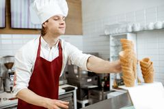Salesman selling ice cream in the shop. Handsome salesman in apron and hat taking waffle cones while making ice cream at the modern pastry shop royalty free stock images