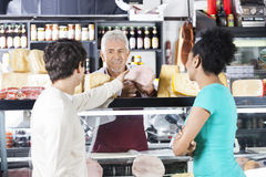 Salesman Selling Meat Piece To Couple In Grocery Store. Smiling senior salesman selling meat piece to couple in grocery store Stock Photo