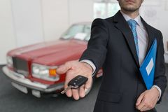 Salesman is selling a new car and passing keys royalty free stock photos