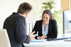 Salesman selling to a client at office. Salesclerk talking trying to convince to a happy client in a desktop at office Royalty Free Stock Photography