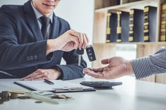Salesman send key to customer after good deal agreement, success. Ful car loan contract buying or selling new vehicle stock image