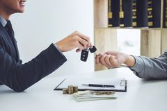 Salesman send key to customer after good deal agreement, success. Ful car loan contract buying or selling new vehicle royalty free stock image