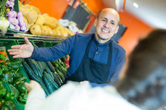 Salesman serving buyer purchasing veggies Stock Photography