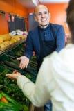 Salesman serving buyer purchasing veggies Stock Photos