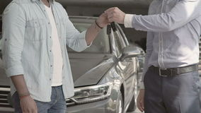 The salesman shakes hands with buyer after buying the car. The salesman shakes hands with buyer. The seller gives him a keys from a new car. Two men are shaking stock video