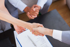 Salesman shaking hand with client. With contract on the coffee table Stock Image
