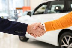 Salesman shaking hands with client in car dealership. Closeup royalty free stock photos